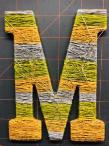 TIe off Threads Wrapped around Wooden Letter